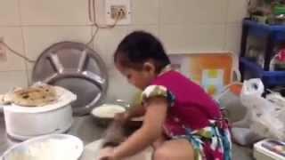 Small baby child girl making roti herself
