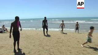 African migrants play football with Italian children, having survived harrowing sea journey