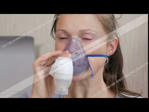 Young woman holding a mask from an inhaler at home. Treats inflammation of the airways via nebulizer