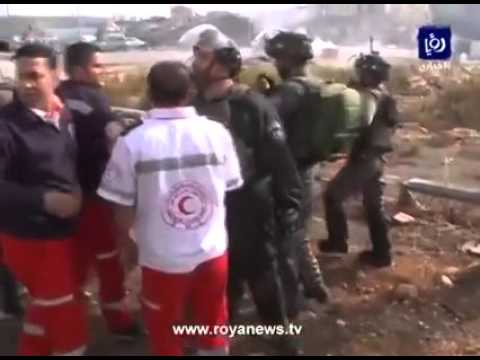 Israeli soldiers over run a Palestinian and prevent the medic teams from giving him help