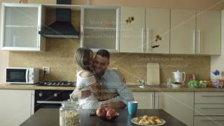 Attractive young couple embracing and kissing early morning in the kitchen while man have breakfast