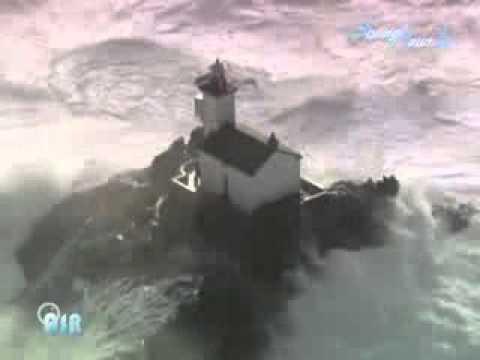 increible tomenta con olas gigantes chocando contra faros en la costa