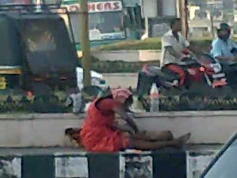 Poverty in India-A mother is bathing her baby in a busy traffic in Cochin