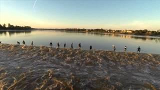 Line of Surfers Surfing Tidal Wave Aftermath on Saint Pardon