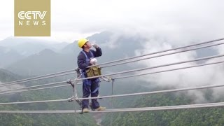 Men on wire: Power workers walk in the clouds to repair lines