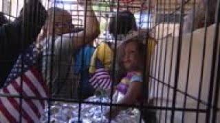 Protesters carry cages with dolls inside