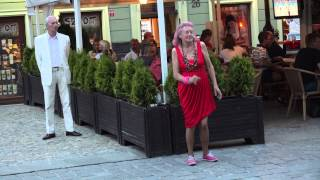 Old and drunk woman dancing in the street