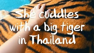 She cuddles with a big tiger in Thailand