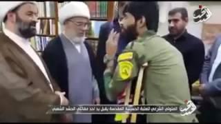 شاهد من خلال الفيديو ممثل المرجعية الدينية العليا يحاول ان يقبل يد احد ابطال الحشد الشعبي المقدس   Y