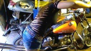 Girl kick starts motorcycle