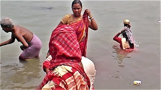 Mother bathing her son in the river Ganges on holy occasion