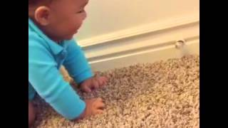 Cute baby laughs while playing with a spring door stop