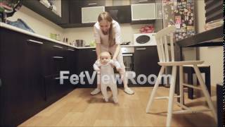 Young mother dances with a small baby in the kitchen