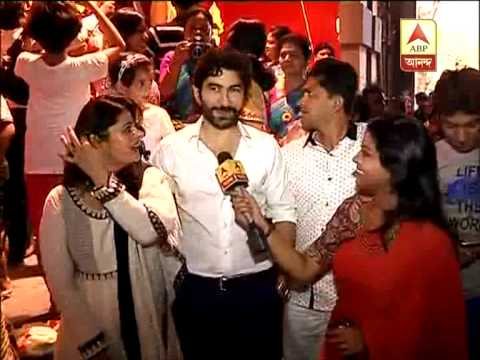 Actor Jeet alongwith wife speaking on puja vacation at a pandal.