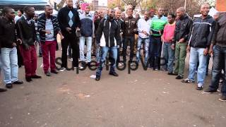 Extreme long shot. A male choir sings as people gather to...