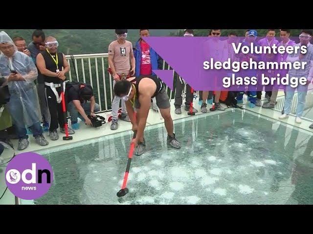 Volunteers sledgehammer glass bridge to test strength