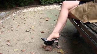A sexy girl dangling with high heels in a park