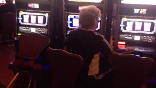 Greedy old lady playing 3 slot machines