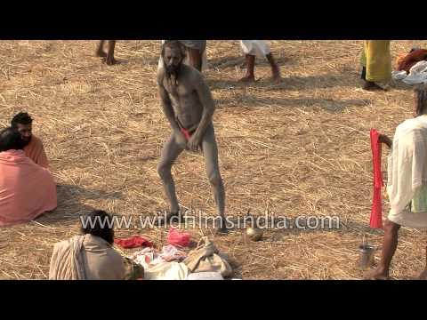 Sadhu baba smears his body with ash