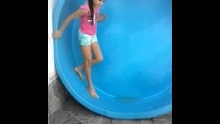 Menina cai na piscina.