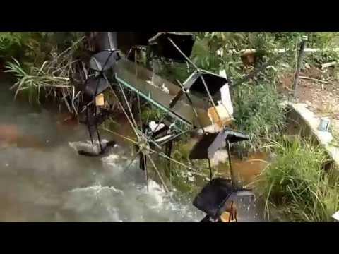Roda d agua movida pela correnteza do rio funcionando com rio cheio. Eleva a água