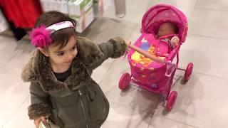 Little Girl Pushing Pink Stroller in Shopping Centre