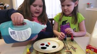 Kids mixing milk, food coloring and dish soap