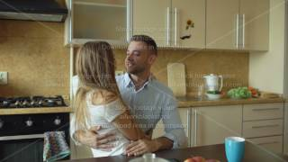 Attractive young couple meet early morning in the kitchen embracing and kissing together