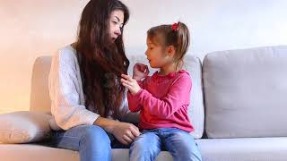 Beautiful young mother with little daughter sitting on sofa, baby playing with woman hair