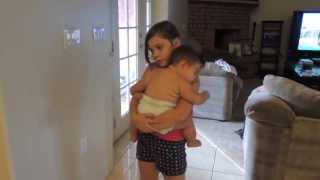 Big sister putting little sister to sleep