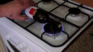 Open a bottle of wine using a gas stove