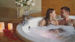 Adorable young couple is having fun and talking in bubble bath during romantic honeymoon. Romance