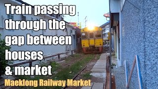 Train passing through the gap between houses & market