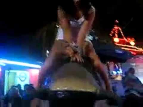 Garota de mini saia no touro mecânico Segura peão