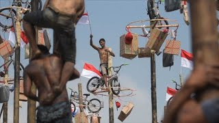Men take part in traditional greasy pole contest at Asian Games