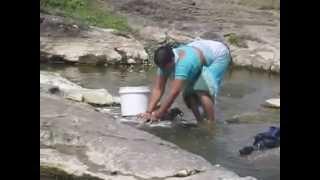 A LADY WASHING CLOTHES NEAR RIVER SIDE AT SINNAR, NASHIK, MAHARASHTRA, INDIA