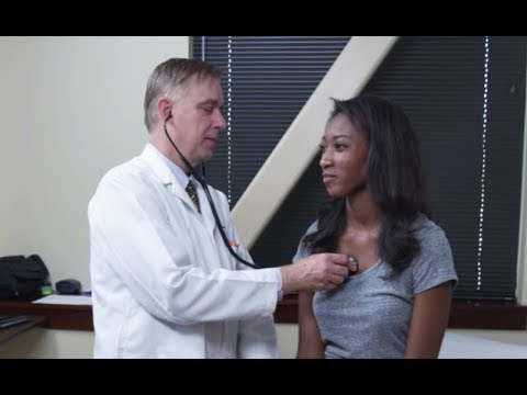 Doctor examining young woman's heart rate and breathing, 4K video