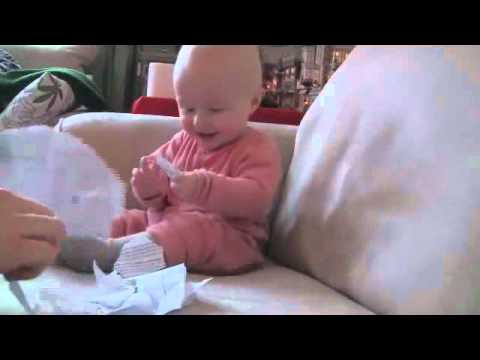 Bebé ríe mientras su padre rompe un papel