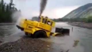 A Russian tractor driver refuses to give up after his vehicle gets stuck in a river.