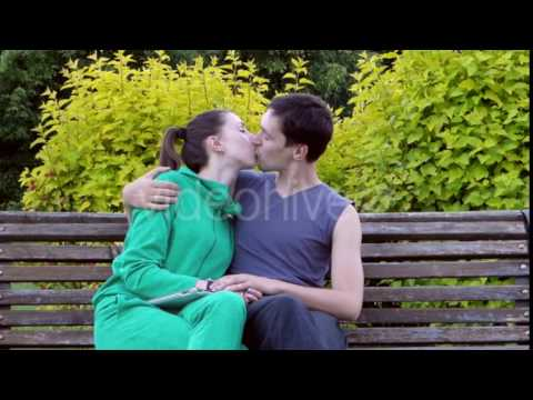 Xxx Mp4 Beautiful Young Couple Sitting Resting On A Park Bench They Hug Each Other And Kiss 3gp Sex