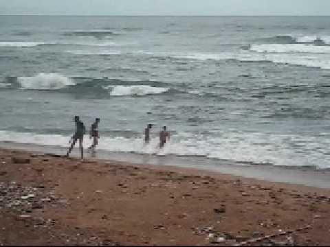Niños bañándose en la playa de Güibia agua muy sucia en Santo Domingo