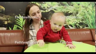 A young mother sits at a table in a cafe and plays with the baby