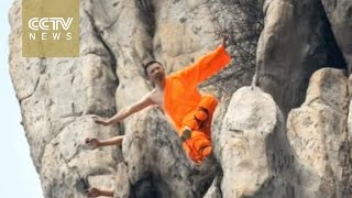 Kung fu masters show off their skills on a cliff