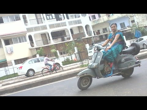 Indian woman ride on scooter in Saree