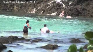 Tourists washed off rocks by big wave