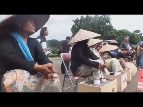 Women cement their feet protesting new factory construction in Indonesia