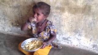 Slum girl enjoying her egg meal