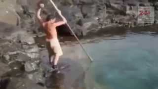Catching huge fish by a spear in the beach