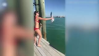 Woman grabs onto distressed seagull to free it from plastic wound