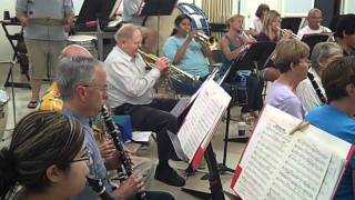 """Dixieland Jam!"" incorporates several pieces: ""Basin Street Blues,"" ""Maple Leaf Rag,"" ""Tin Roof Blues,"" ""When the Saints Go Marching In,"" and ending with ""Bill Bailey."" Arranger: Bob Lowden   A group of five soloists, plus drums, contrasts with the full band. Our soloists are, in score order, Sydney Funderburk, clarinet; Deb Fiedler, Tenor Sax; Jerry Green, trumpet; Susan Collins, Trombone; Curt Allen, Jr., Tuba. Les Murad plays the drums.   A technical note: When the camera was close to the drumset, it automatically lowered the volume, such that the band fades into the background and even the soloists are somewhat attenuated."